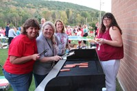 c v staff members smile as they work to grill up hot dogs for rally in the valley event