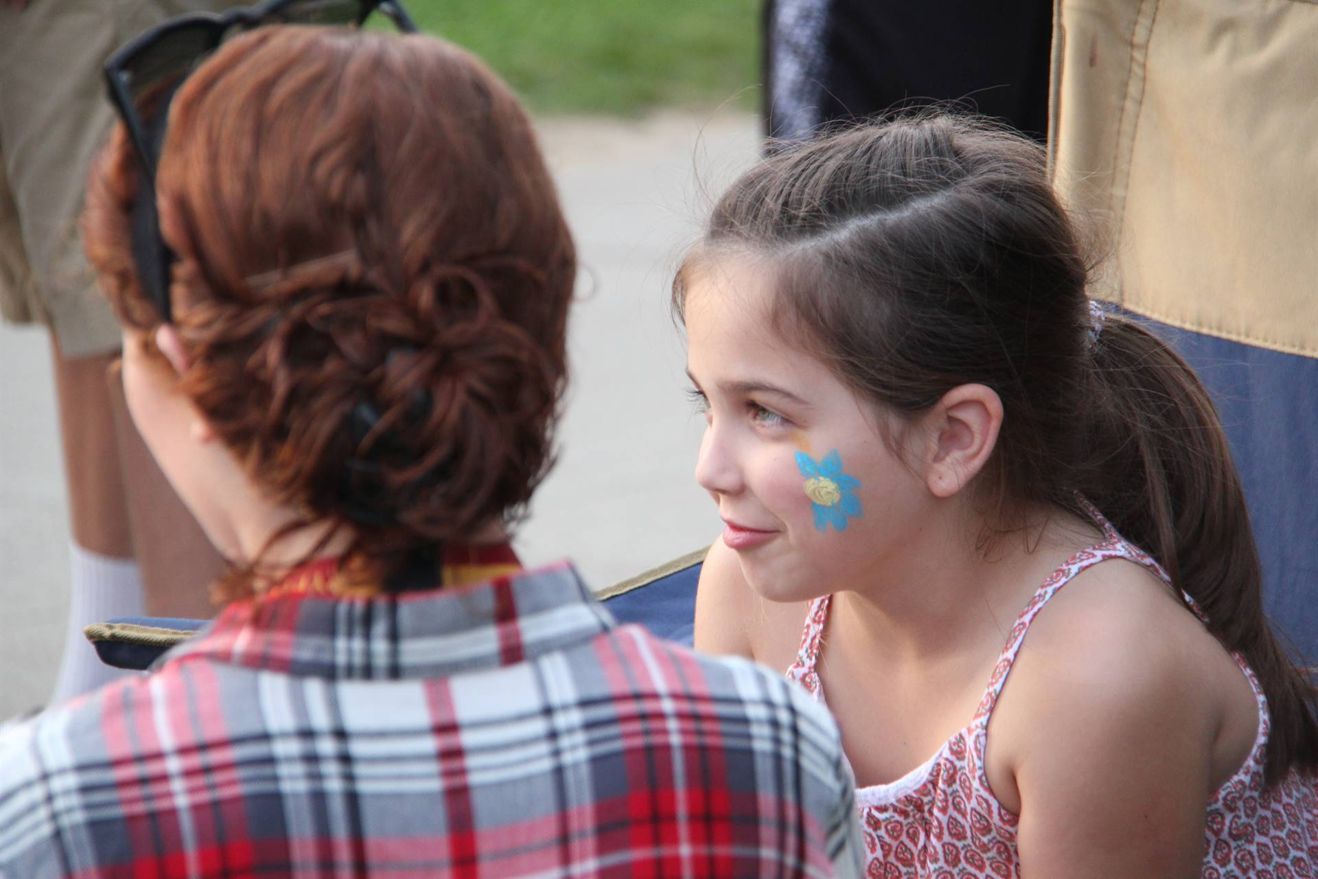 younger student gets her face painted by high school student