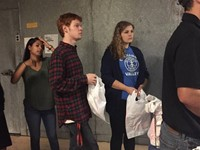 interact club officer peter jensen and mia hause stand in line to help fill bags for backpack progra