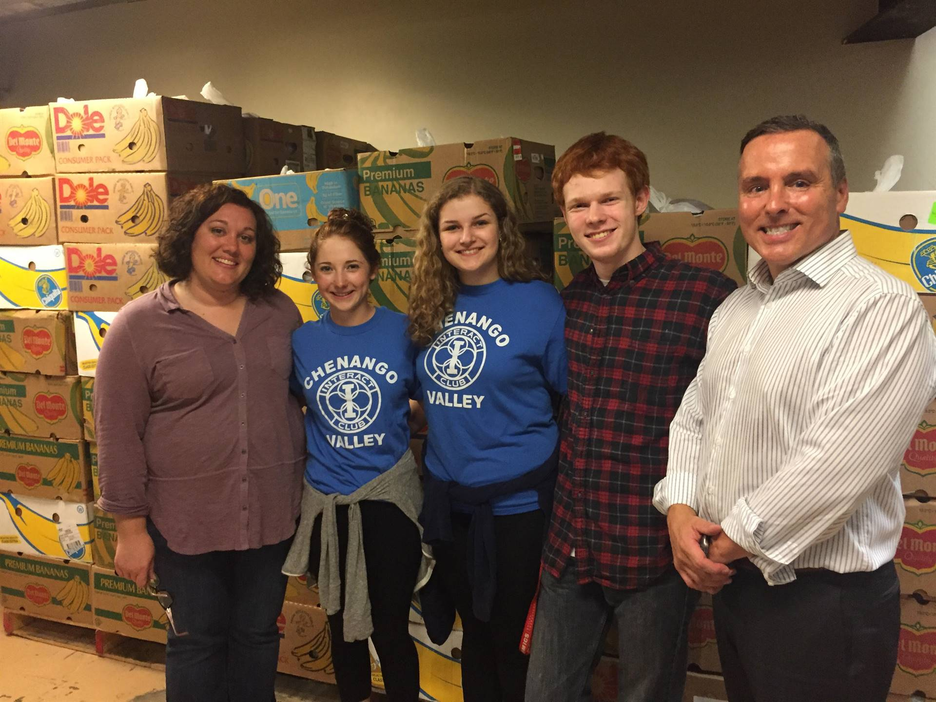 interact club officers smile in front of filled boxes with c v teacher anne marie griffin and superi