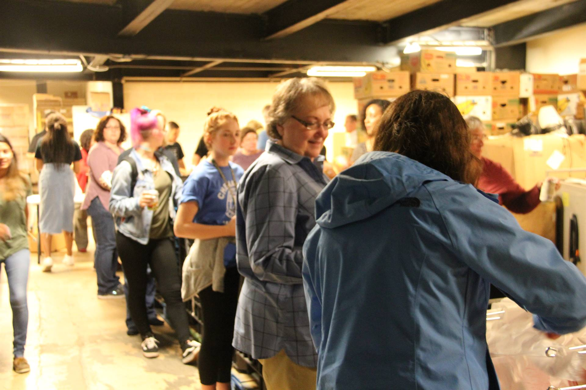 line of people helping to fill bags of food for backpack program
