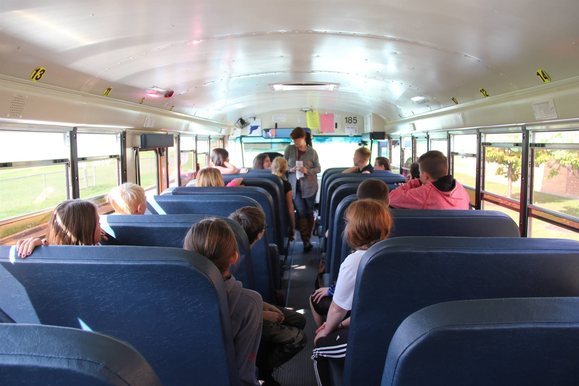 far shot from back of bus of bus driver talking to middle school students during bus drill