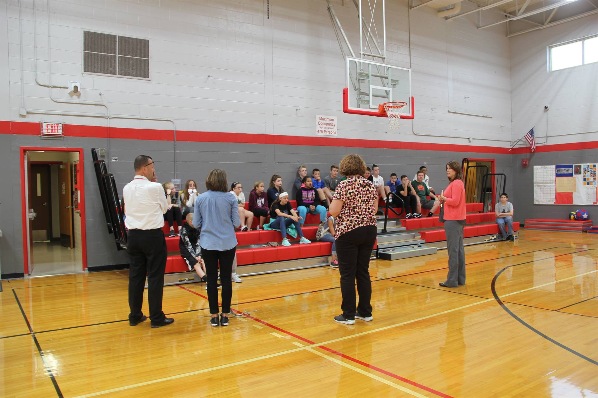 far shot of c v staff talking to students in middle school gymnasium