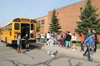 far shot of students lined up after exiting back of bus for bus drill