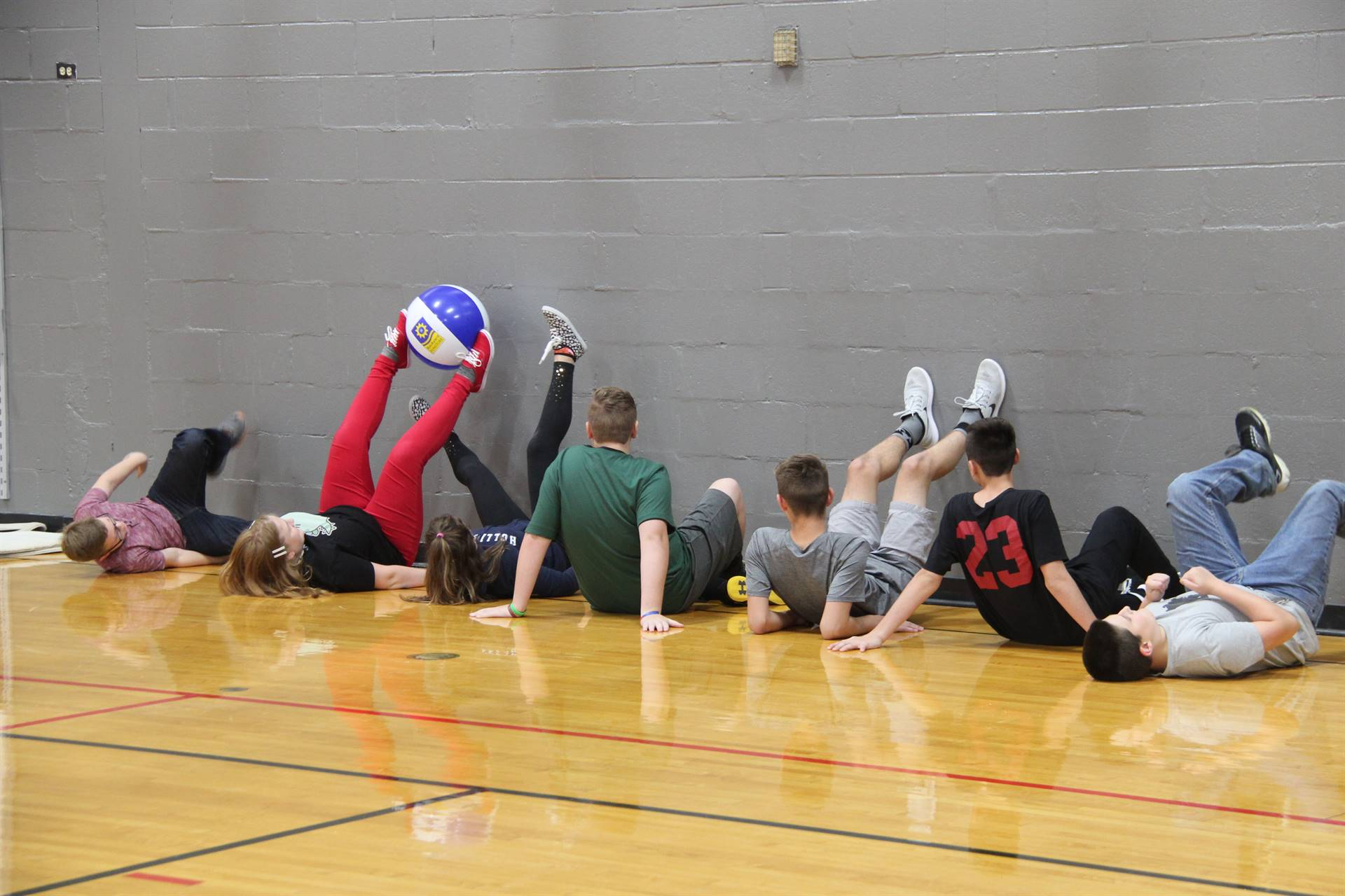 far shot of students working together to move ball with feet for teamwork challenge