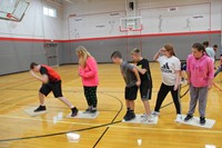 middle school students attempt to return back to other side of gym playing game of lava team buildin