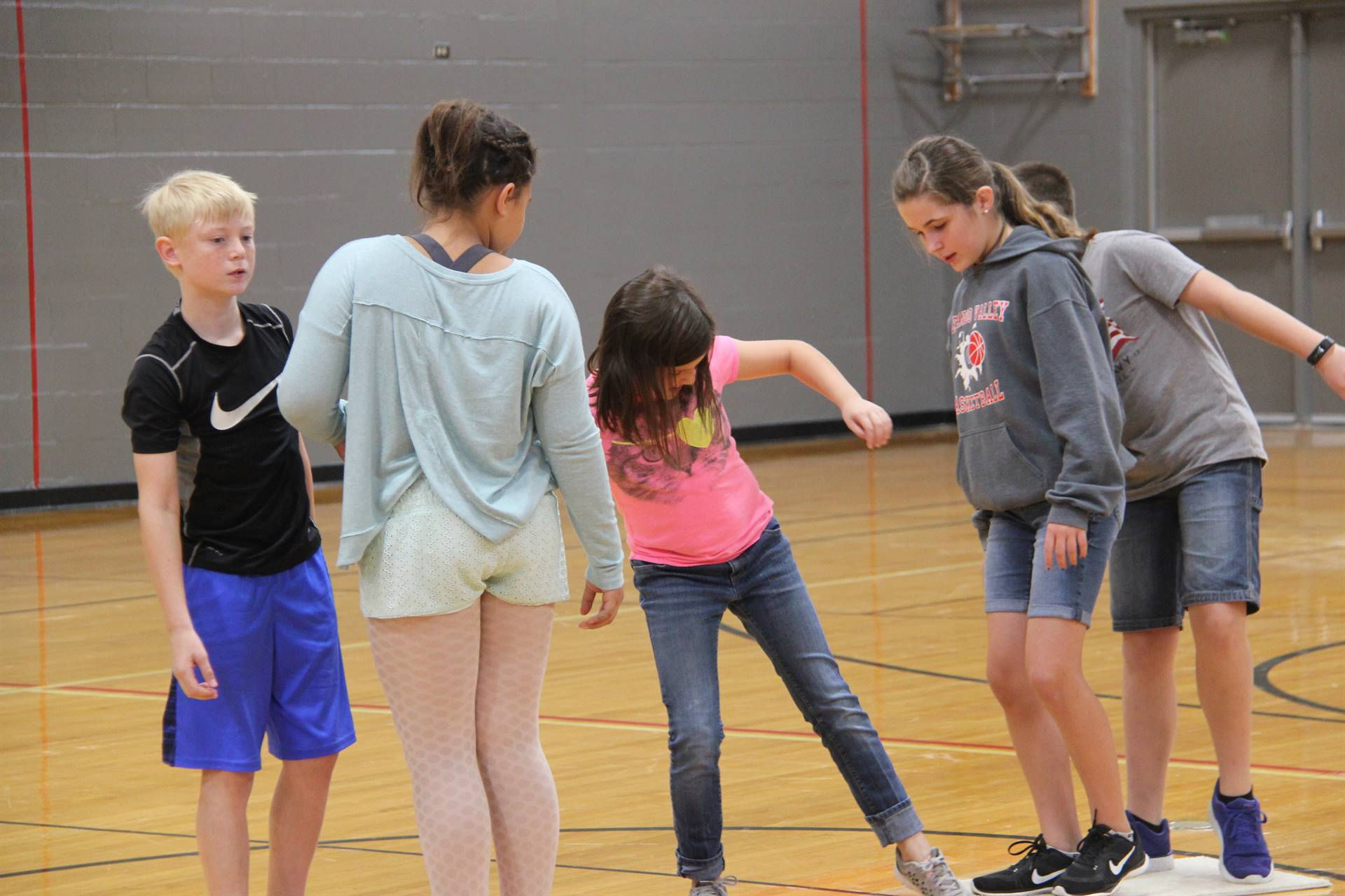middle school students learn team work skills by playing a game of lava