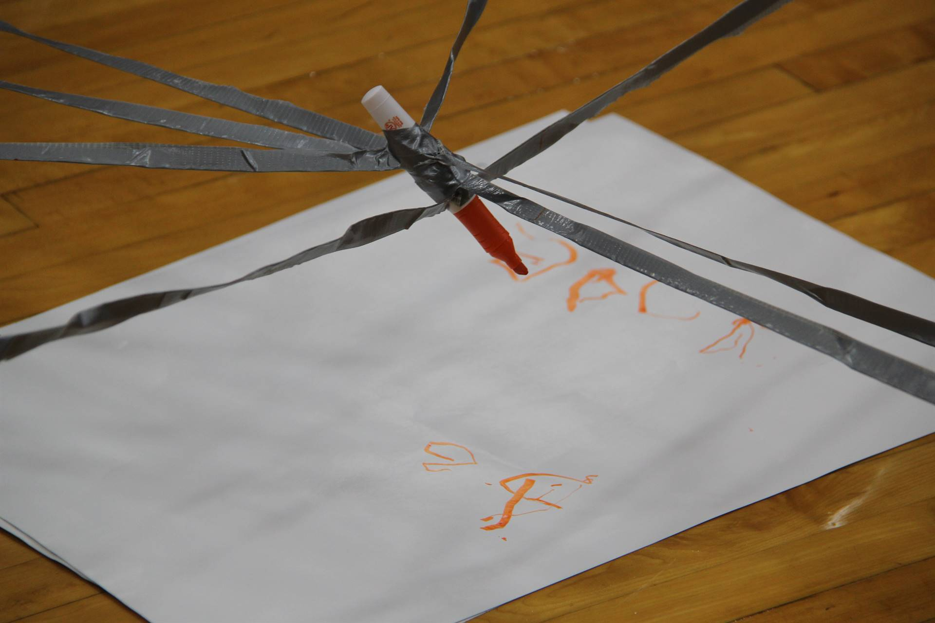 students attempt to use teamwork to write positive message using long strands of masking tape
