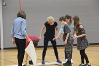 students work to get back to the other side in lava team building game challenge