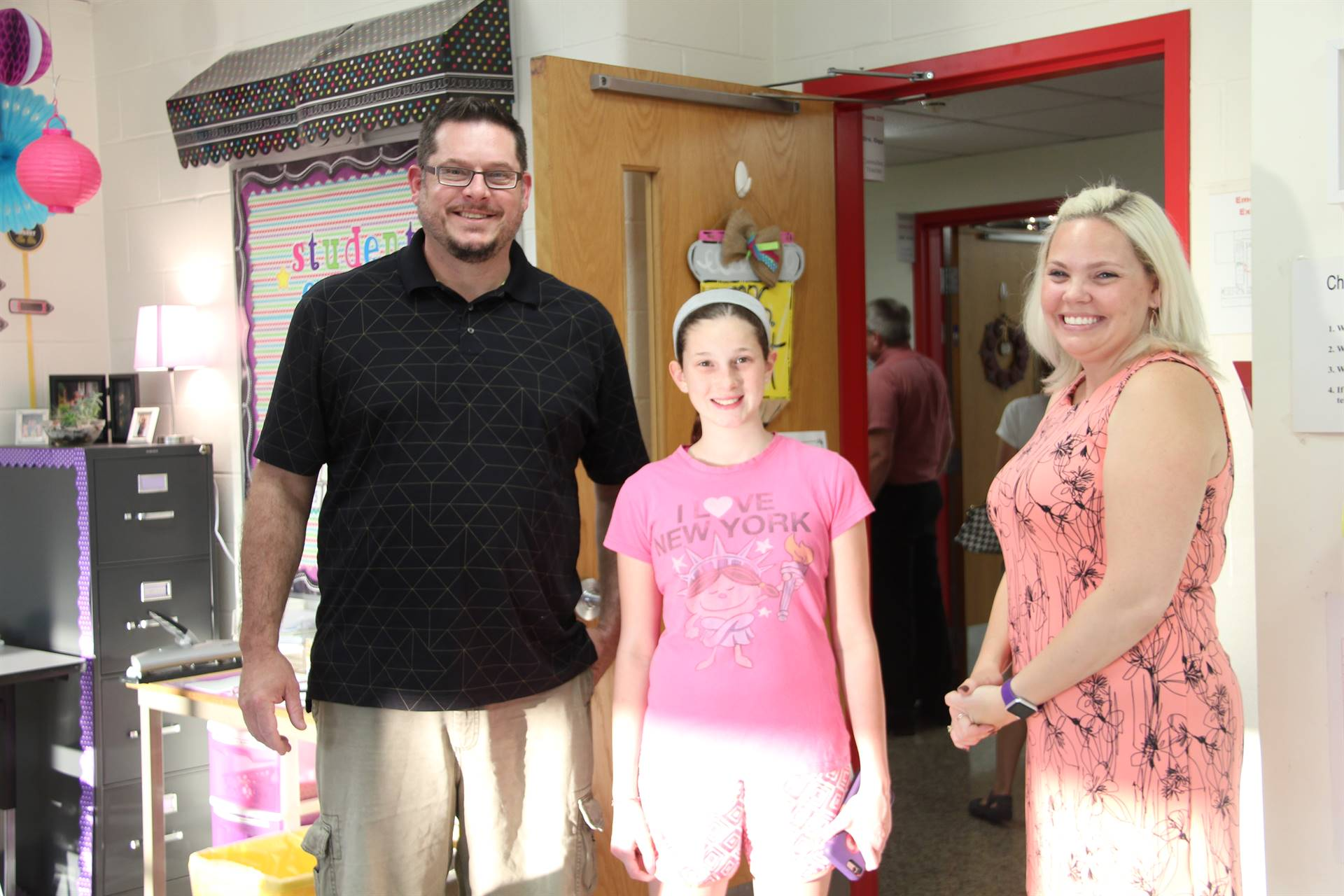teacher smiles with parent and student at middle school open house