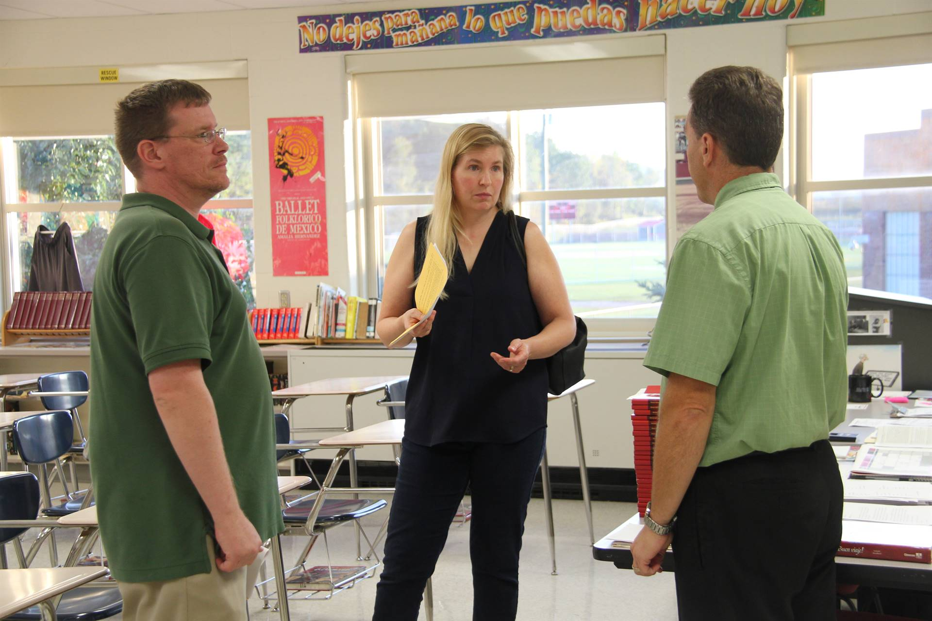 teacher talks with two guardians at middle school open house