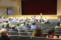 principal attleson talks to parents and guardians at middle school open house in auditorium