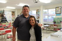 teacher smiles for a picture with parent who is a c v coach during open house