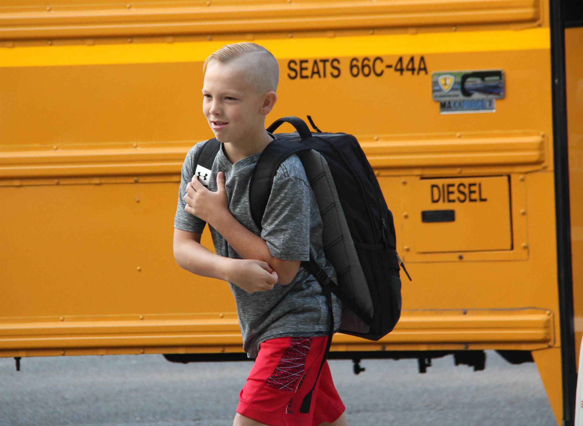boy smiles after getting off school bus walking towards elementary school on first day