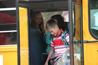 boy smiles getting off the bus to go to first day of school at chenango bridge elementary