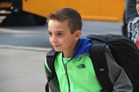 boy smiles walking towards elementary school on first day