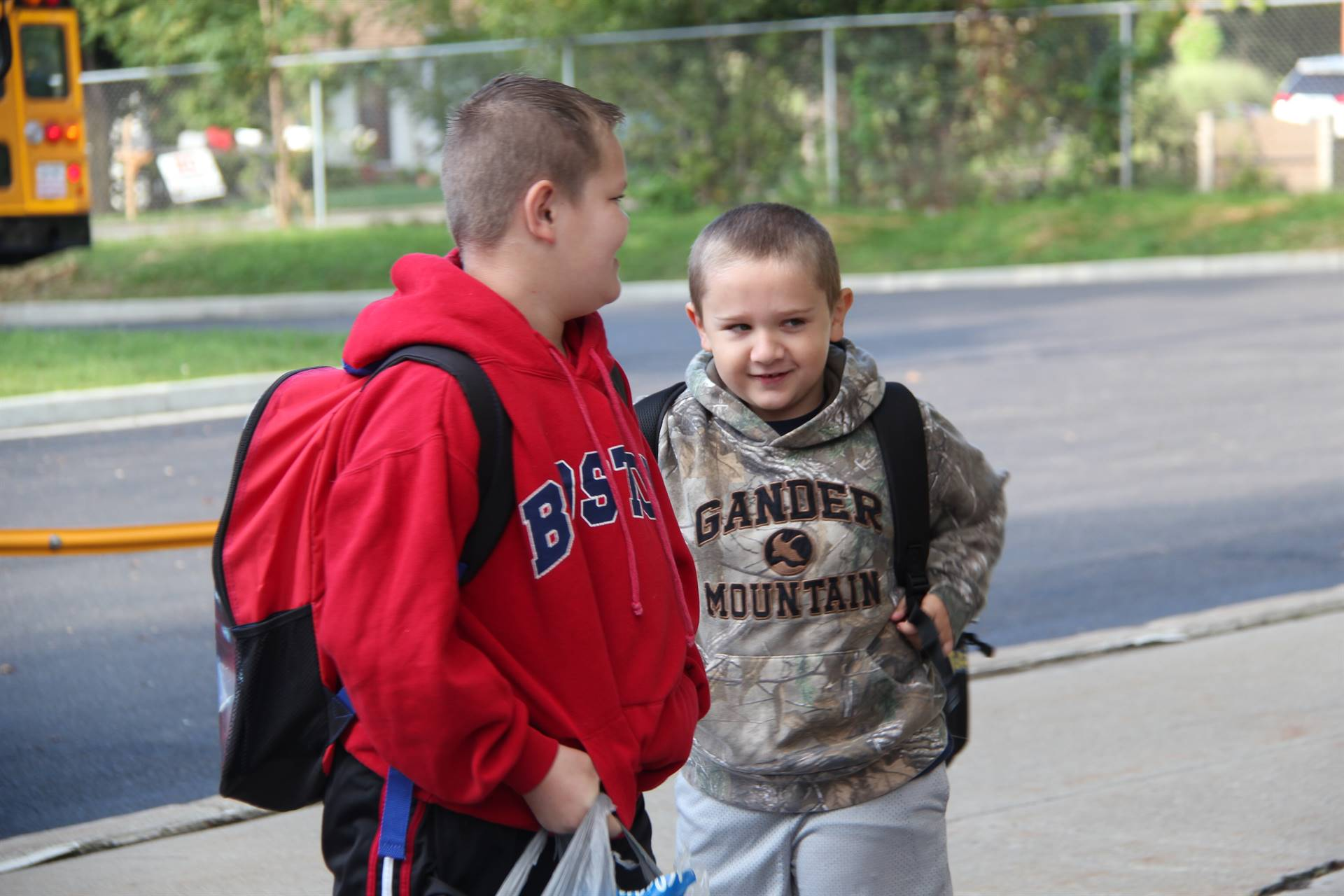 boys smile standing outside of chenango bridge elementary school on first day