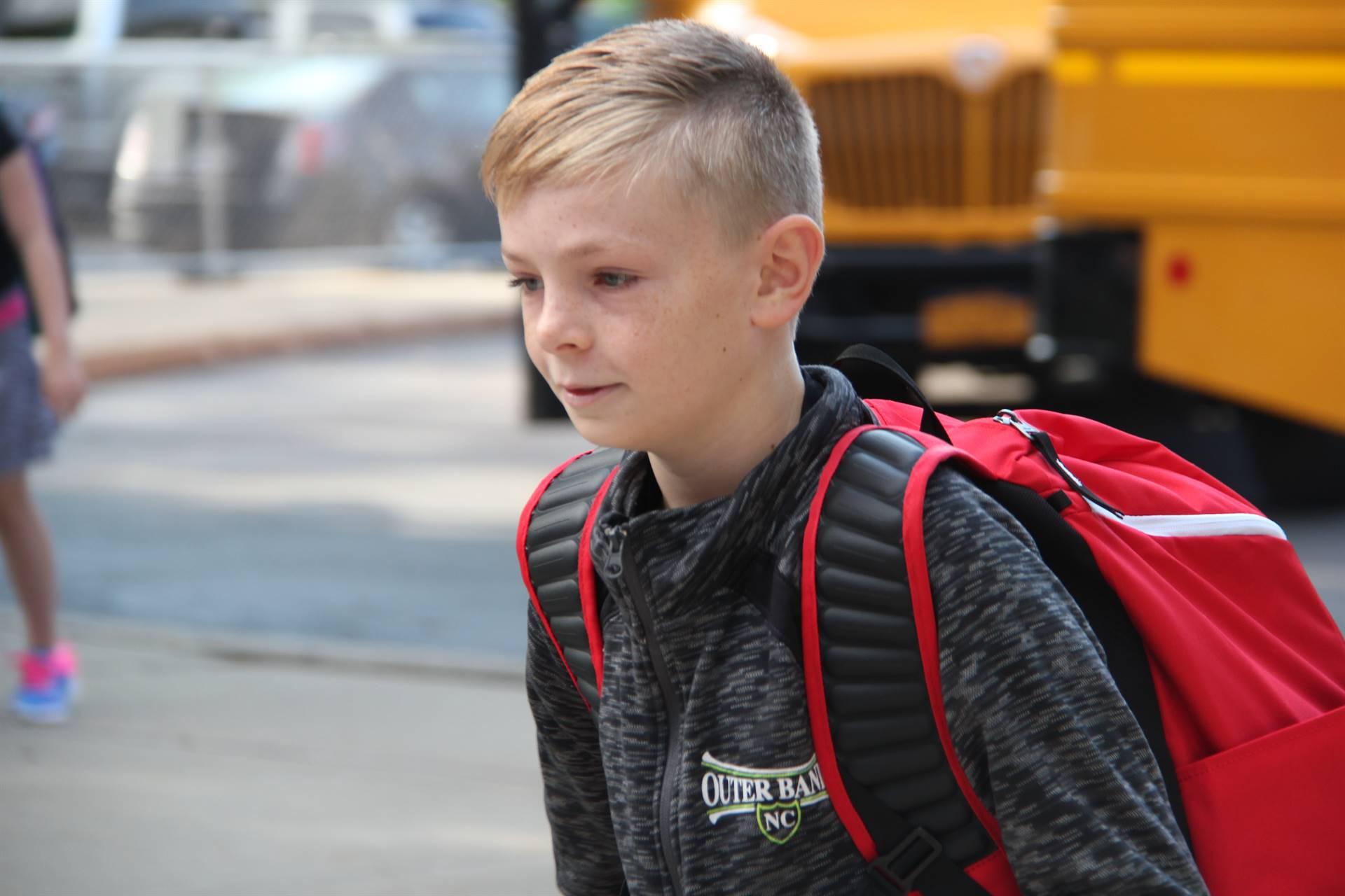 boy smiles walking towards chenango bridge elementary school