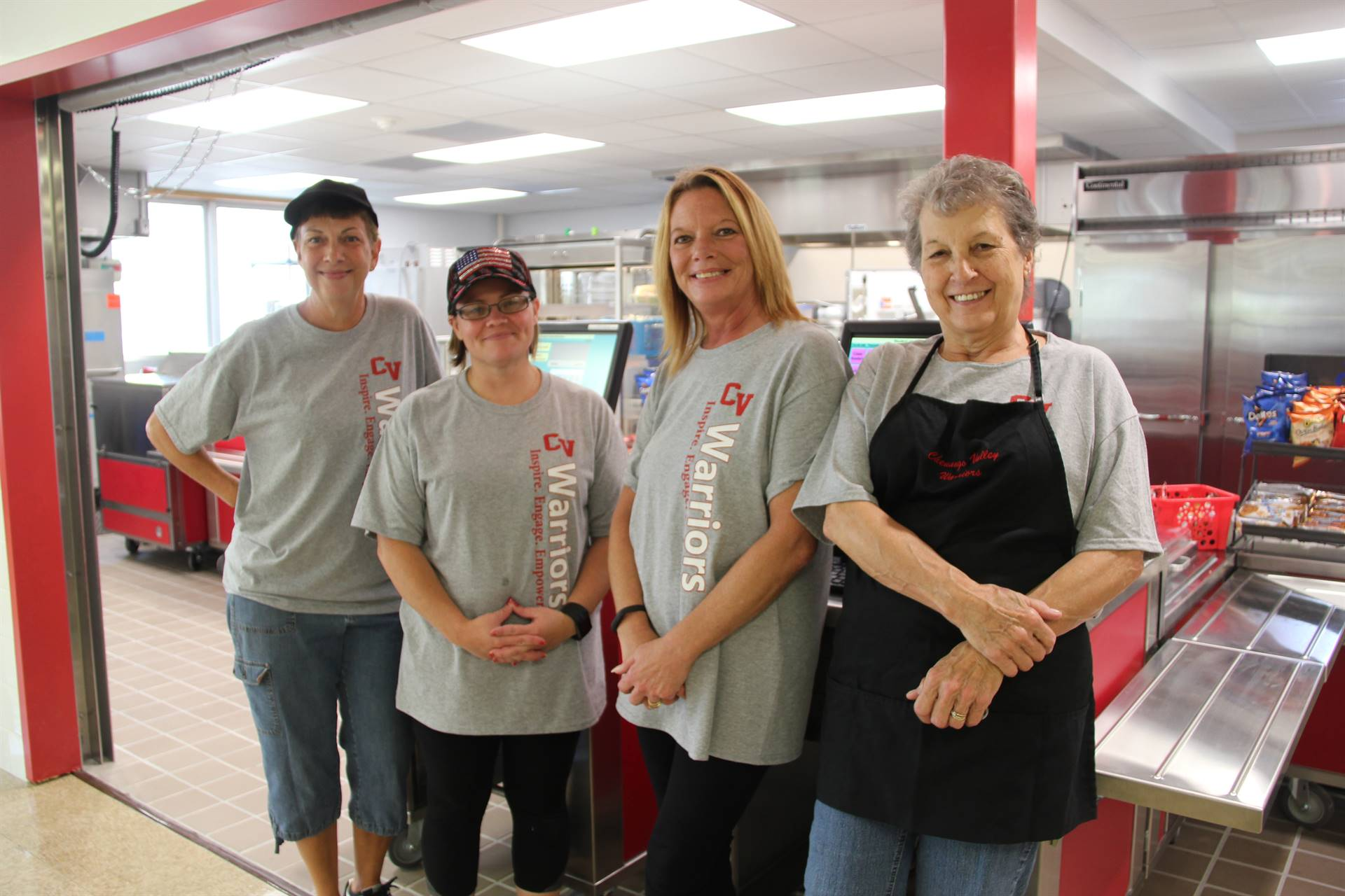 chenango bridge food services staff smiles in front of renovated cafeteria kitchen