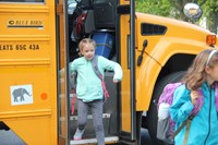 girl smiles getting off her bus at chenango bridge elementary on the first day of school