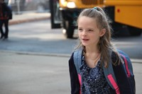 girl smiles walking towards school on first day