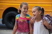 girls smile talking to each other walking towards chenango bridge elementary on first day of school