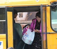 student exits school bus smiling