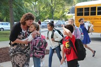 student hugs principal mary beth hammond while another student waves hello on first day of school