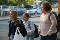 three girls smile walking towards chenango bridge elementary after getting off bus on first day of s