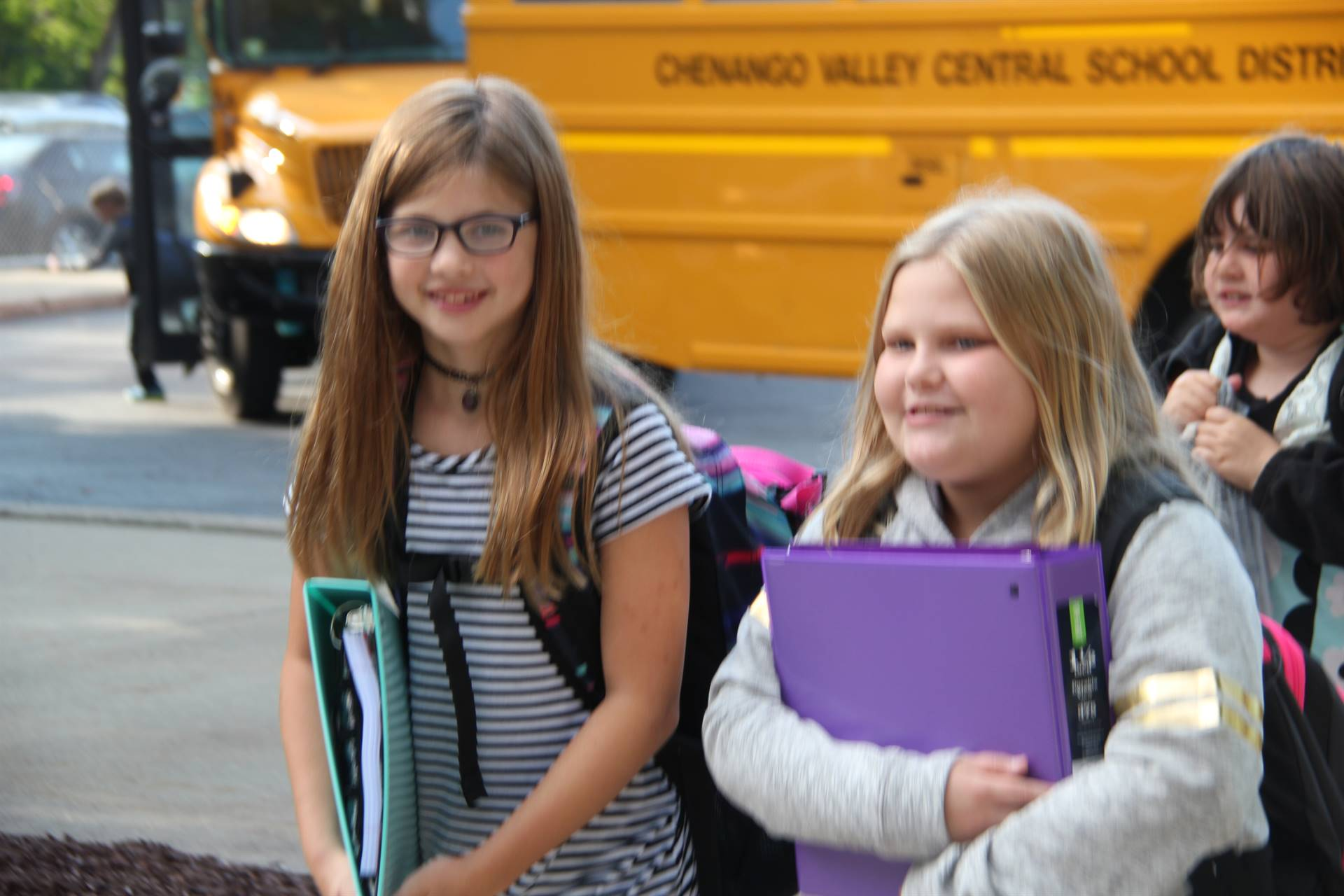 two girls smile walking towards elementary school on first day