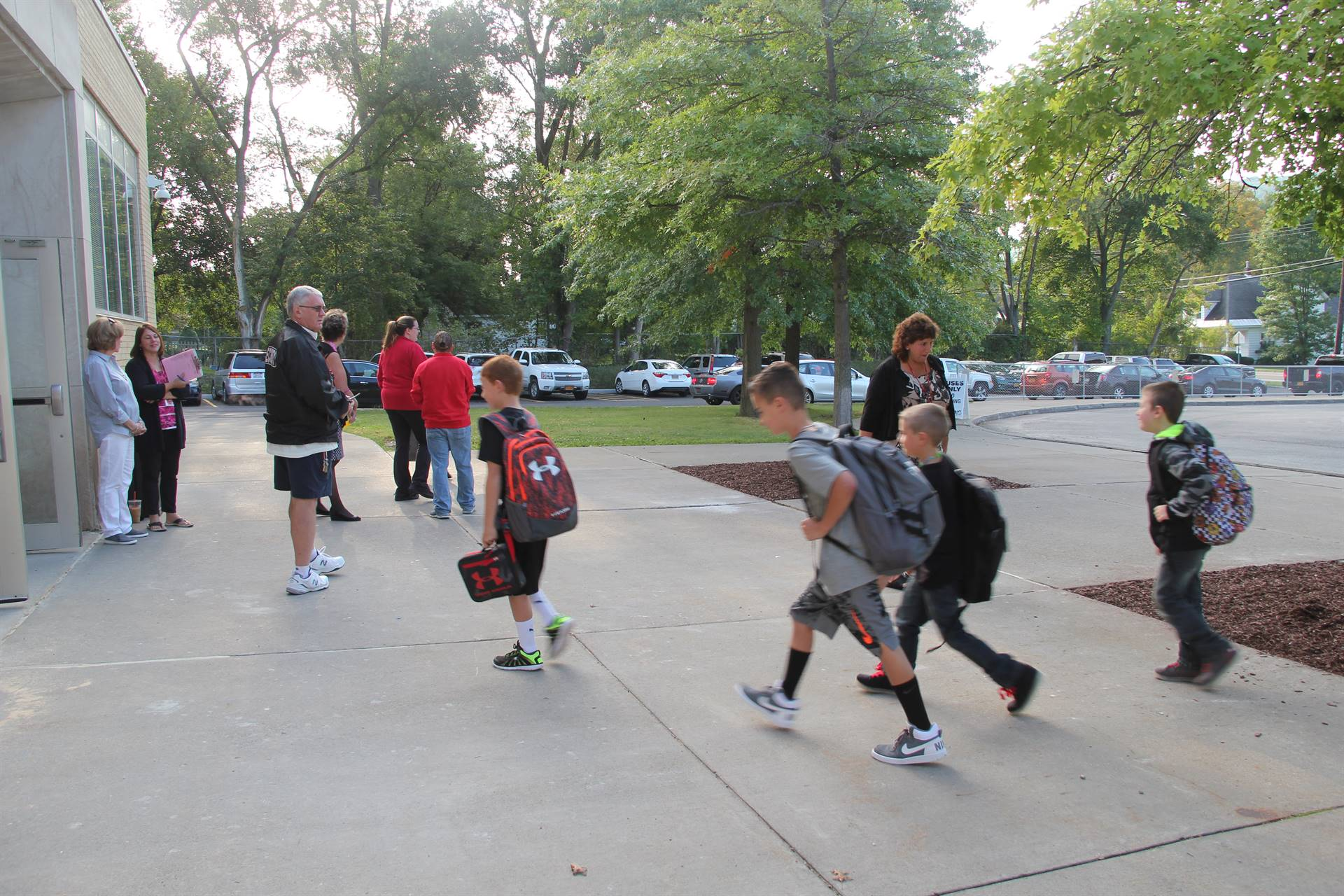 wide shot of elementary students walking towards school on first day