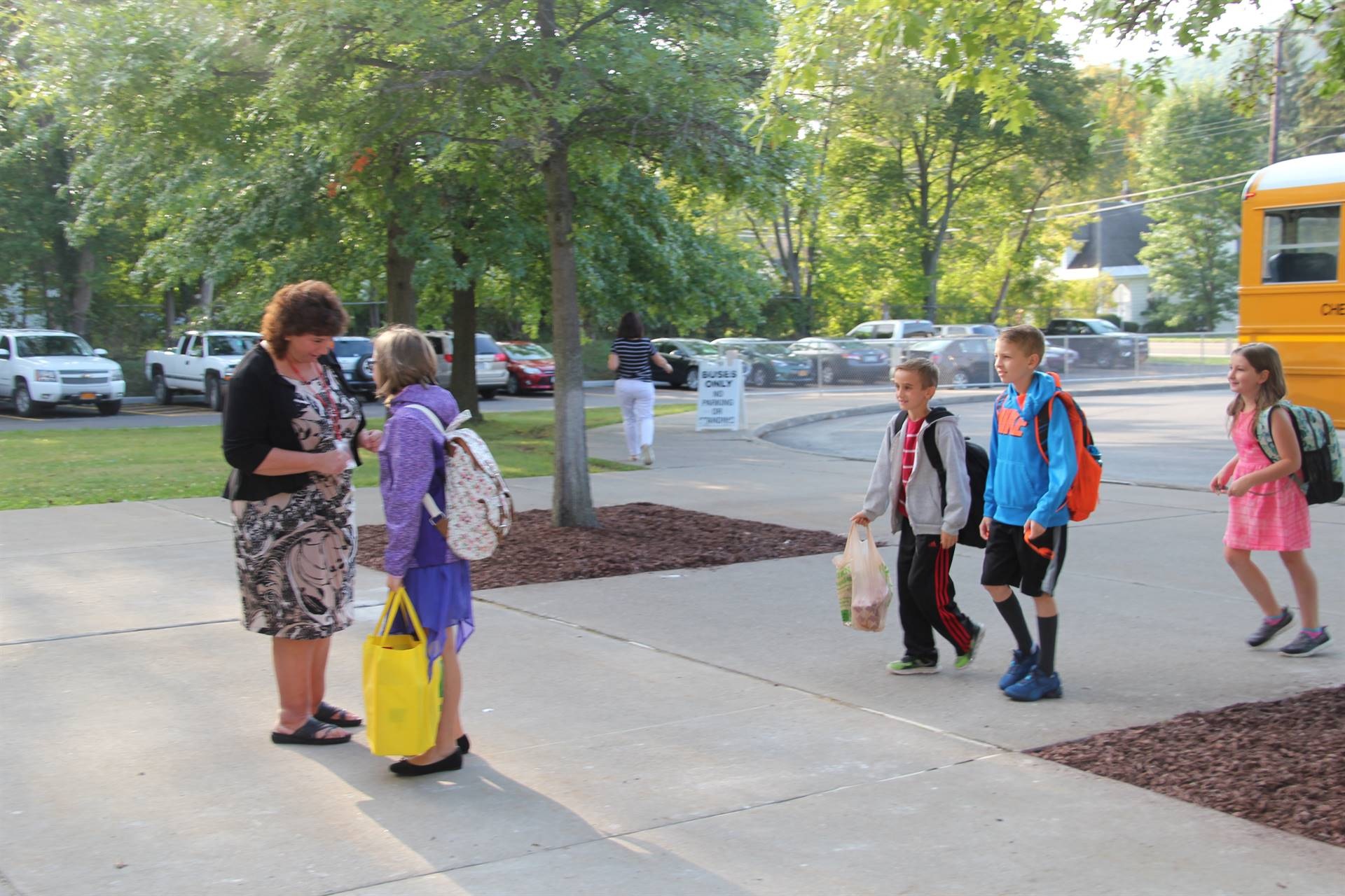 wide shot of student stopping to speak with principal mary beth hammond before entering elementary s