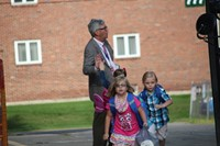 students walk towards elementary school and student gives principal jim pritchard a high five in the
