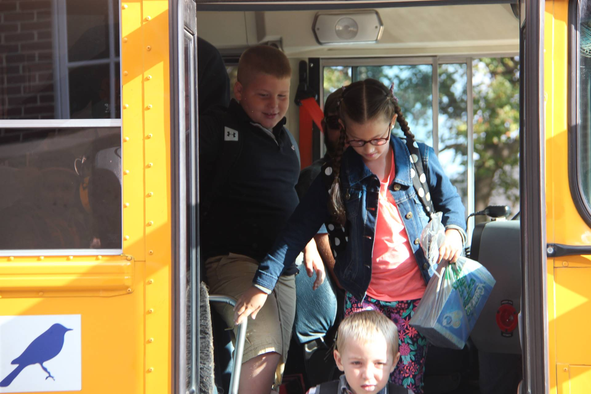 students smile getting off bus