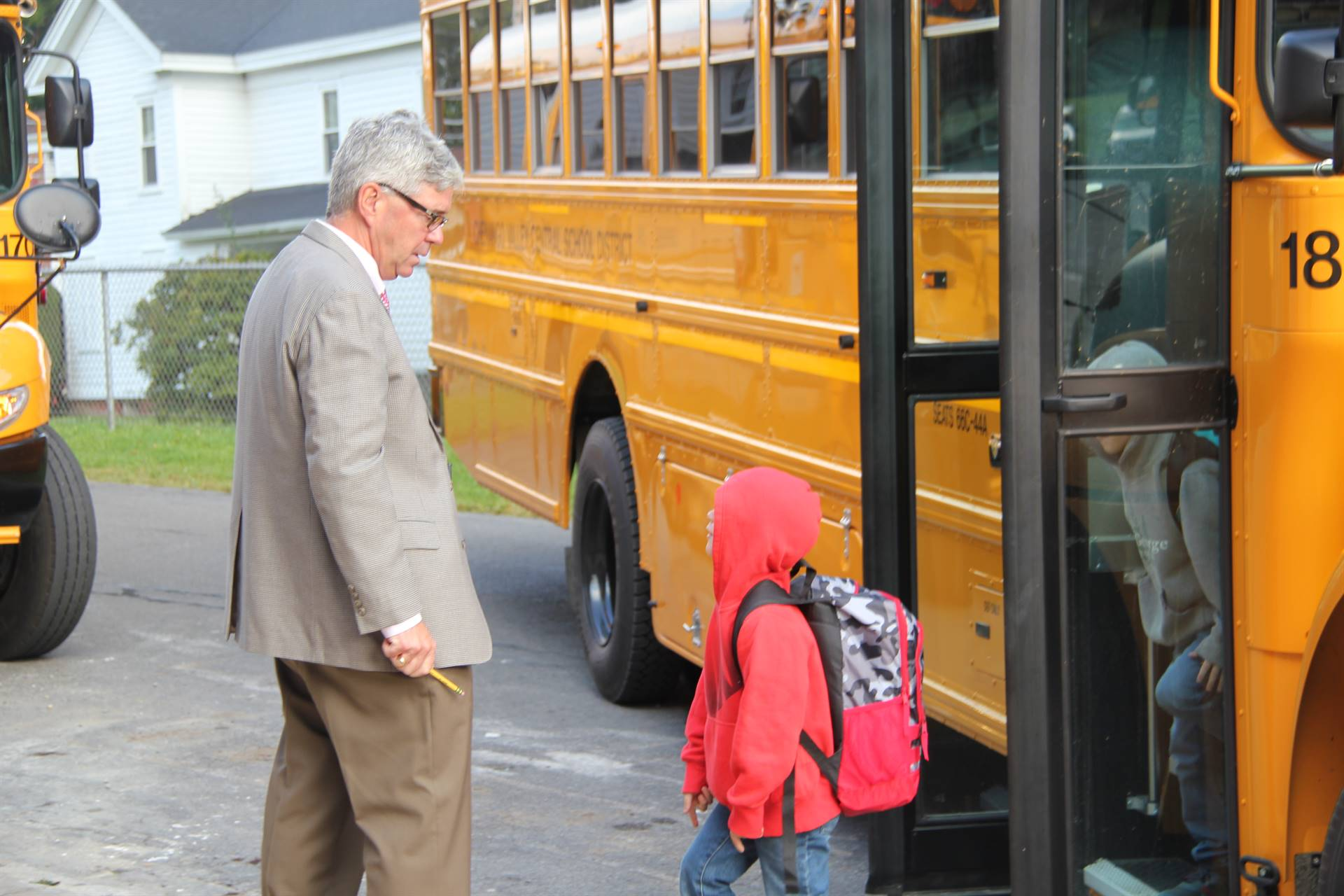 principal jim pritchard welcomes students getting off bus to elementary school
