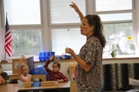 teacher asks question and students raise their hand to answer question