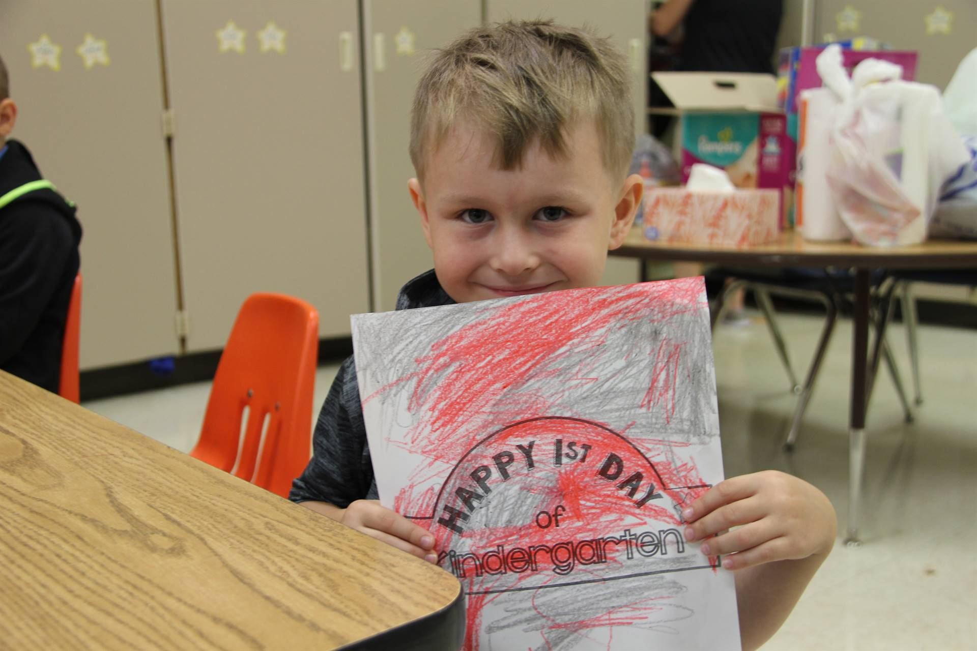 student holds up picture he colored that says happy first day of kindergarten