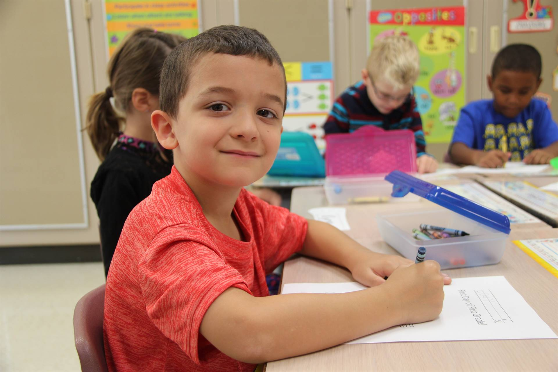 student takes a moment to smile while coloring at port dickinson elementary