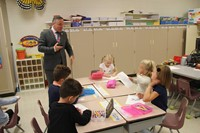 students show superintendent gill their coloring