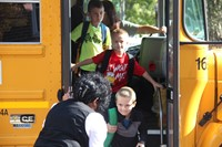 teacher greets students off bus on first day of school
