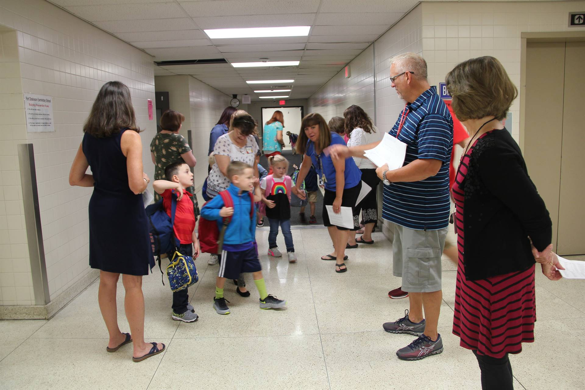 teachers greet students in port dickinson hallway
