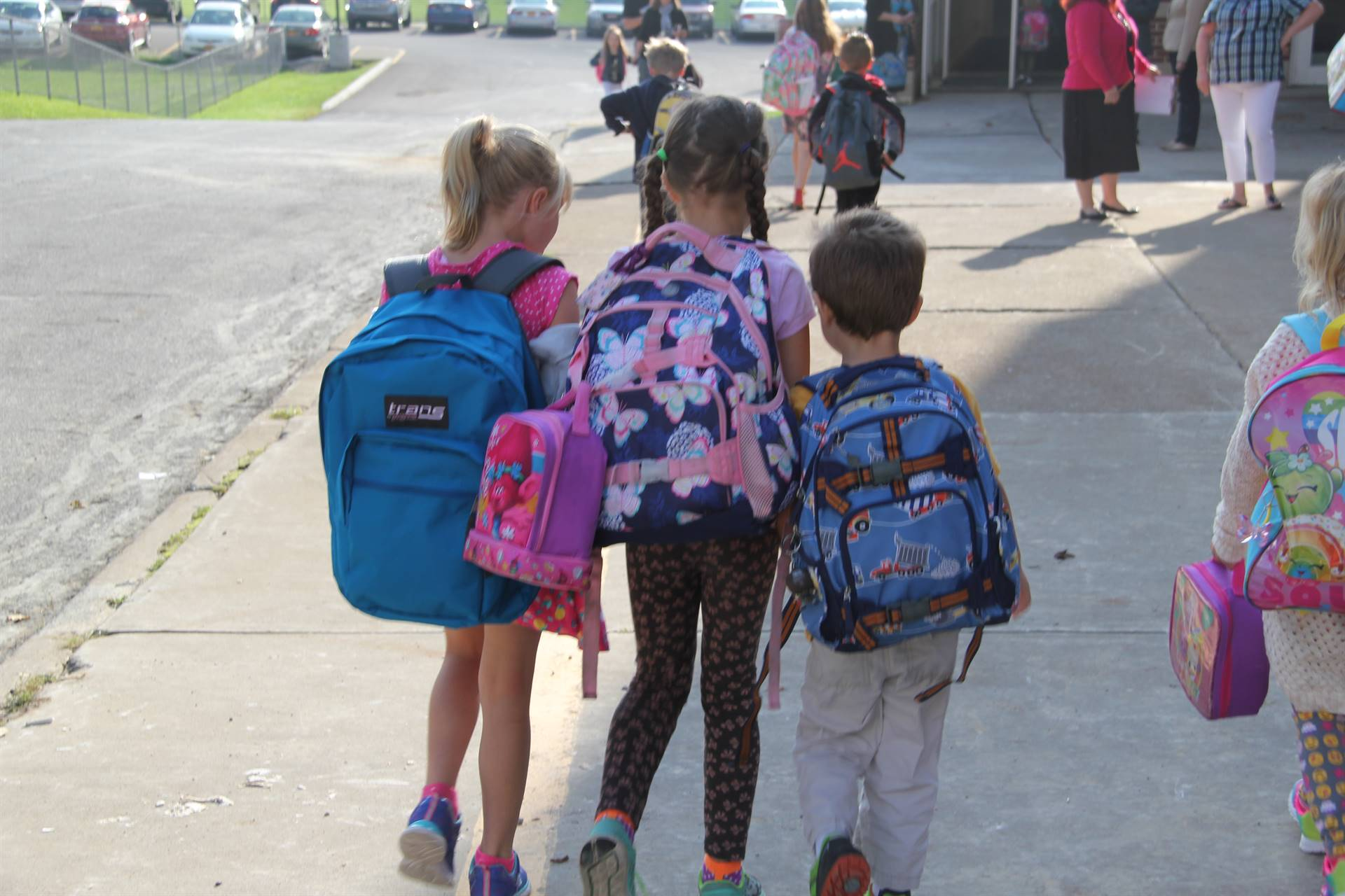 three students hold hands walking towards elementary school