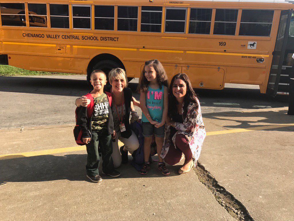 teachers at port dickinson elementary in front of buses with students