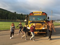 more middle school and high school students getting off the school bus on the first day