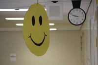 big smiling face sign outside of classroom