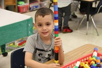 boy smiles next to lego tower he made on first day of school