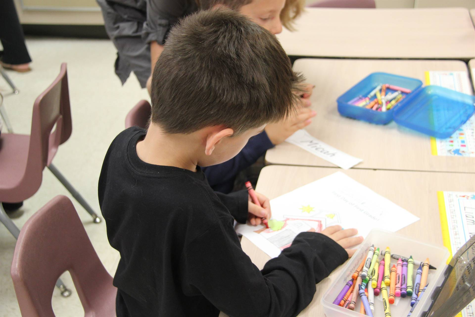 boy coloring on first day of school