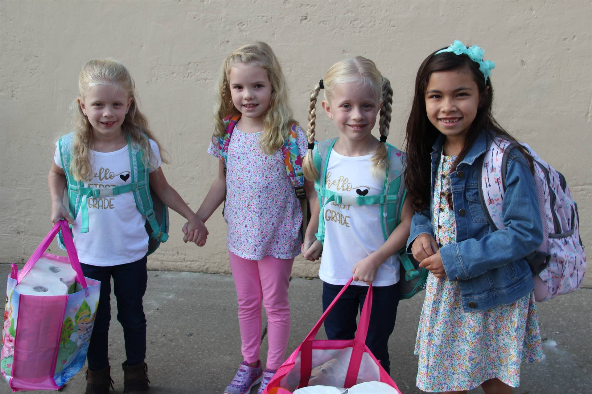 four girl students smile on first day of school