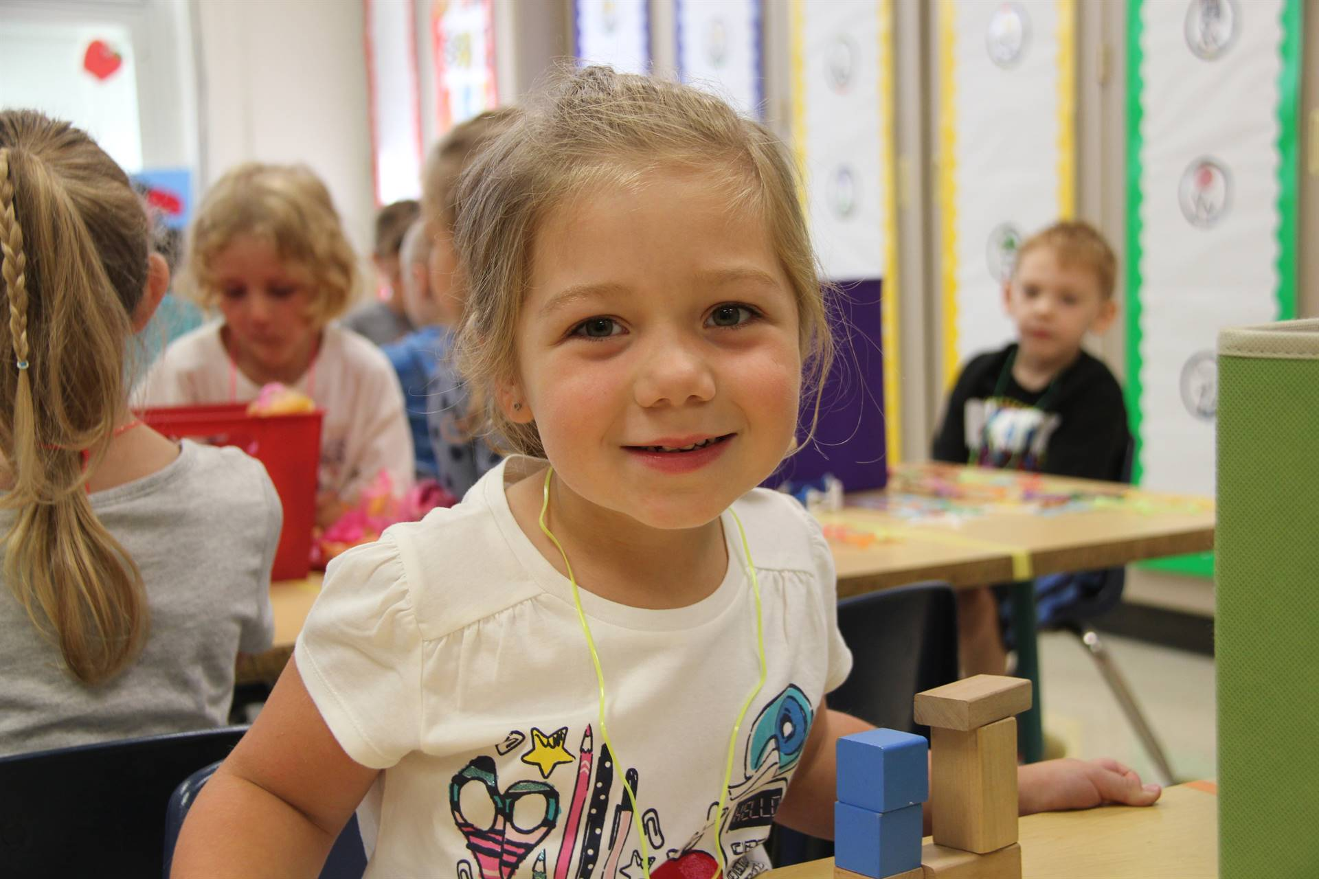 girl smiles sitting in classroom on first day of school