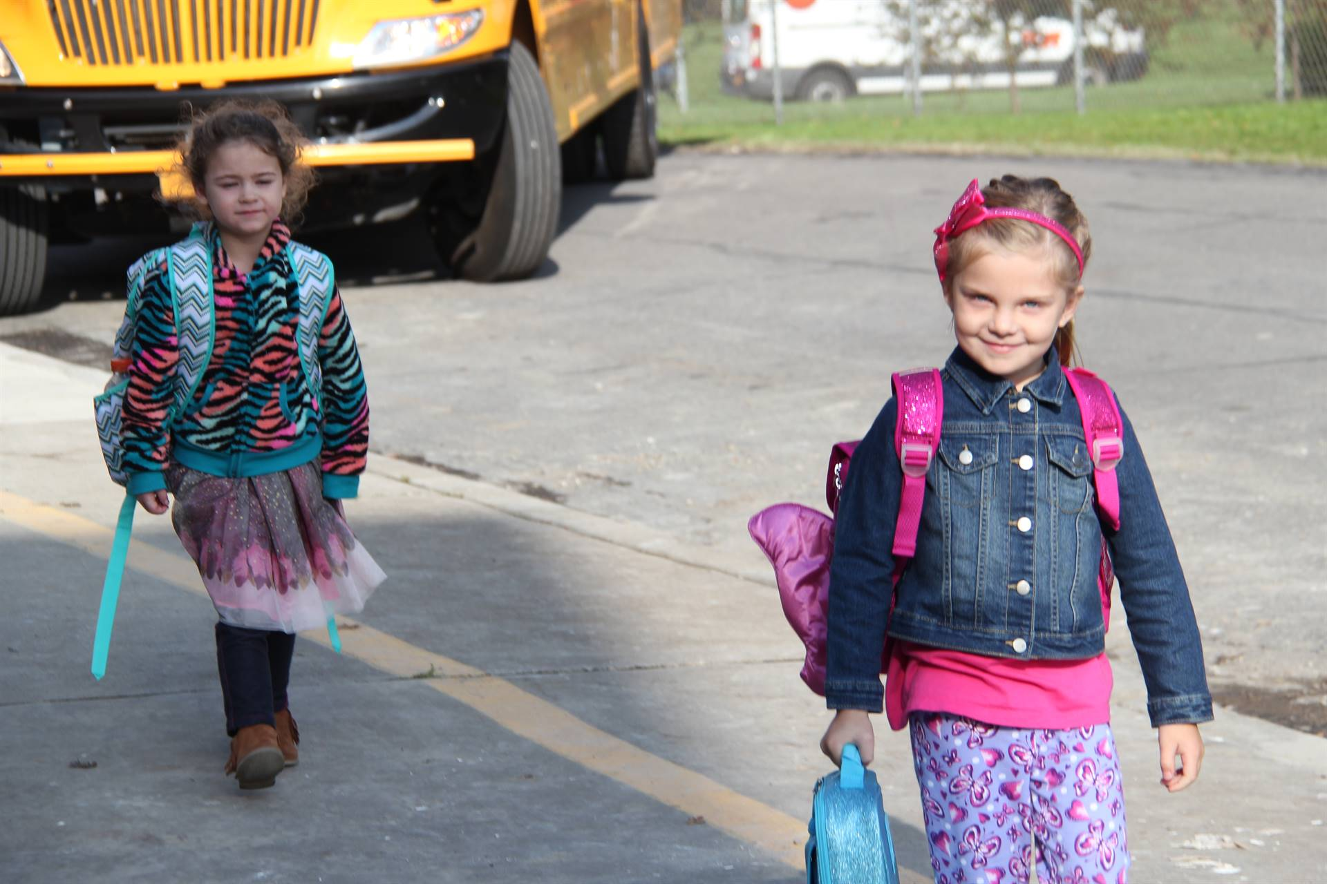 girls smile while walking towards port dickinson elementary school after getting off bus